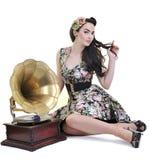 Lyssnande musik för nätt flicka på den gammala grammofonen arkivbild