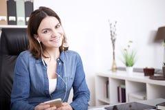 Lyssnande musik för nätt kontorskvinna från telefonen royaltyfri fotografi