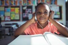 Lyssnande musik för pojke med hörlurar på skrivbordet arkivbilder