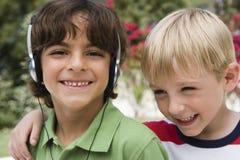 Lyssnande musik för pojke med vännen royaltyfri foto