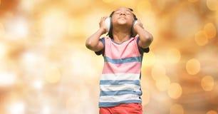 Lyssnande musik för pojke till och med hörlurar över bokeh Arkivbilder