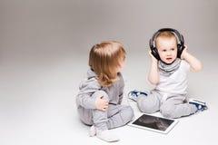 Lyssnande musik för små syskongrupper på hörlurar arkivfoton