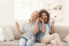 Lyssnande musik för två kvinnor och delahörlurar royaltyfria bilder
