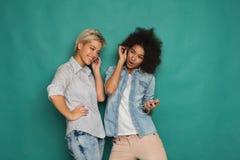 Lyssnande musik för två kvinnor och delahörlurar royaltyfri fotografi