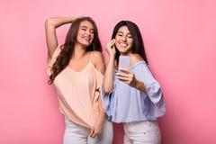 Lyssnande musik för två kvinnor som är online- på smartphonen royaltyfria foton
