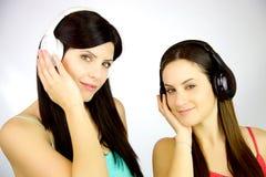 Lyssnande musik för två unga kvinnor med hörlurar med mikrofon Fotografering för Bildbyråer