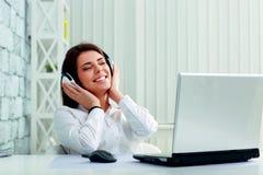 Lyssnande musik för ung gladlynt affärskvinna i hörlurar arkivbild