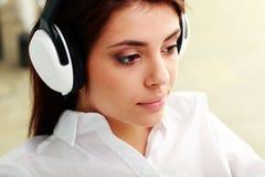 Lyssnande musik för ung härlig affärskvinna royaltyfria foton
