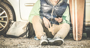 Lyssnande musik för ung hipsterman på den smarta telefonen för mobil på bilturen arkivbilder
