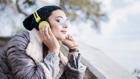 Lyssnande musik för ung kvinna i utomhus arkivfoton