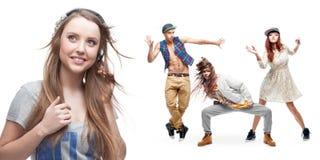 Lyssnande musik för ung kvinna och grupp av dansare på bakgrund Royaltyfria Bilder