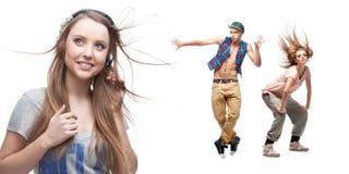 Lyssnande musik för ung kvinna och två dansare på bakgrund Royaltyfri Bild