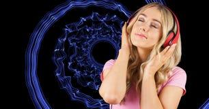 Lyssnande musik för ung kvinna till och med hörlurar mot abstrakt bakgrund arkivfoto