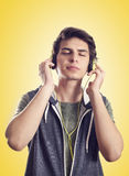 Lyssnande musik för ung man med hörlurar royaltyfria bilder