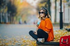 Lyssnande musik för ung nätt flicka för hipster tonårig via hörlurar och att sitta på en trottoar på höststadsgatan och lyssna royaltyfria foton