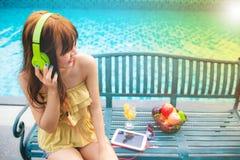 Lyssnande musik för upprymd kvinna med headphonen och att äta det röda äpplet bredvid lycklig och leendebegrepp för swimmimngpool arkivbild