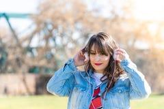Lyssnande musik f?r h?rlig ung flicka utomhus royaltyfri foto