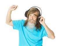 Lyssnande musik för hög man i hörlurar Gamal man med skägget dan Arkivfoto