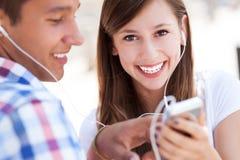 Lyssnande musik för unga par tillsammans Royaltyfria Bilder
