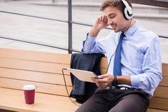 Lyssnande musik och vänta för Businessperson royaltyfria bilder