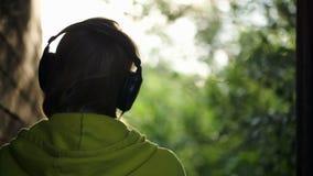 lyssnande musik som är utomhus- till kvinnan arkivfilmer