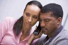 lyssnande nyheterna för par över telefonen till royaltyfri foto