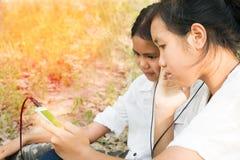 Lyssnande sång för två syster från den smarta telefonen royaltyfri foto