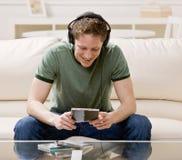 lyssnande sittande sofa för manmusik till Royaltyfria Bilder