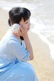 Lyssnande snäckskal för ung japansk kvinna Fotografering för Bildbyråer