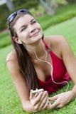 lyssnande spelare mp3 för härlig brunett till kvinnan royaltyfri fotografi