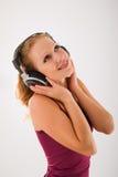 lyssnar den lyckliga hörlurar för attraktiv flicka musen till Fotografering för Bildbyråer