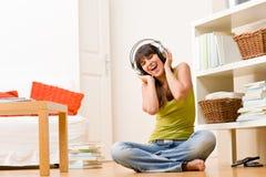 lyssnar den lyckliga utgångspunkten för flickan musik kopplar av tonåringen till Royaltyfri Bild