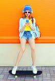 Lyssnar den nätta kalla flickan för mode till musik genom att använda smartphonen på skateboarden över den färgrika apelsinen Arkivbild