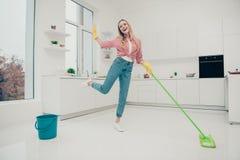 Lyssnar härliga inhemska arbetsuppgifter för fullt foto för längdkroppformat som hon hennes dam tvättar den vita skinande golvdan arkivbilder