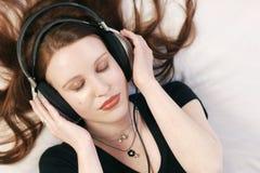 lyssnar musik till Arkivfoto