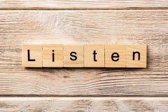 Lyssnar ordet som är skriftligt på träsnittet lyssnar text på tabellen, begrepp arkivfoton