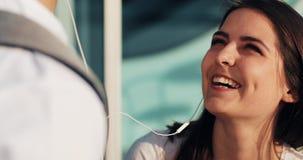 Lyssnar talar den förälskade användande smartphonen för lyckliga par, till musik och till varandra Ungt gift par som har gyckel i arkivfilmer