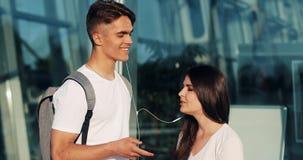 Lyssnar talar den förälskade användande smartphonen för lyckliga par, till musik och till varandra Ungt gift par som har gyckel i stock video