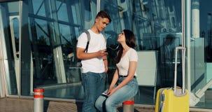 Lyssnar talar den förälskade användande smartphonen för lyckliga par, till musik och till varandra Ungt gift par som har gyckel i lager videofilmer