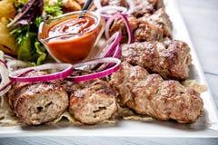 Lyulya kebab με την κόκκινα σάλτσα και το κρεμμύδι άσπρο στενό σε επάνω πιάτων με την εκλεκτική εστίαση Στοκ φωτογραφίες με δικαίωμα ελεύθερης χρήσης
