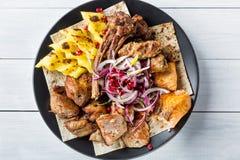 Lyulya kebab, shish kebab, adra na, piec na grillu łosoś ryba, cebuli i granatowa, czarnym talerzu i białym drewnianym stole Odgó Obraz Stock