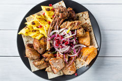 Lyulya kebab, shish kebab, grilled salmon fish, onion and pomegranate grains on black plate and white wooden table. Top view Stock Image