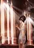 Lyx. Ung kvinna i aftonklänning med exponeringsglas av Champagne Standing på fönstret i solsken Royaltyfri Bild