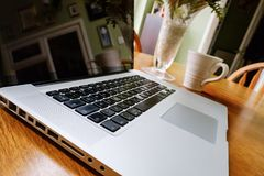 Lyxig bärbar datordator som ses på ett köksbord under ett kaffeavbrott royaltyfri foto