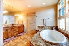 Lyxig badruminre med tegelplattagolvet Det vita badet badar med br Arkivbild