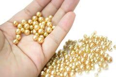 Lyxig bakgrund med guld pryder med pärlor makro i händer Royaltyfri Foto