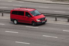 Lyxig bil röda Mercedes Benz Viano som rusar på den tomma huvudvägen arkivfoto