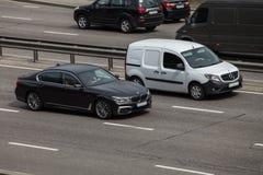 Lyxig bil vita Mercedes Benz vs svarta BMW som rusar på den tomma huvudvägen Arkivfoton