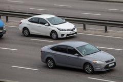 Lyxig bil vita Toyota Corolla som rusar på den tomma huvudvägen royaltyfri foto