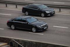 Lyxig bilsvart Mercedes Benz vs svarta Toyota Camry som rusar på den tomma huvudvägen Royaltyfria Bilder